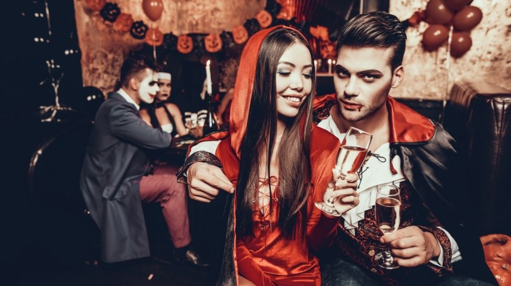 Young Couple Wearing Costumes Drinking Champagne   13 DIY Couples Halloween Costumes: Why Buy When You Can Sew?   featured