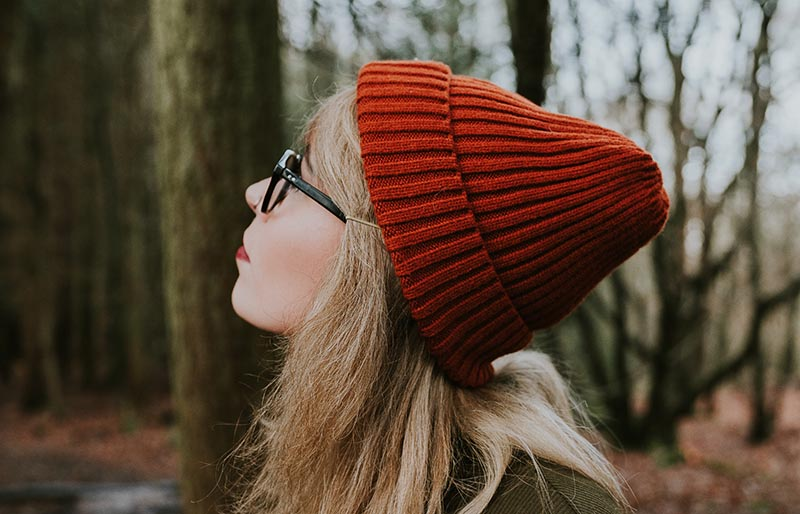 woman in red knit cap and brown sweater | winter trends