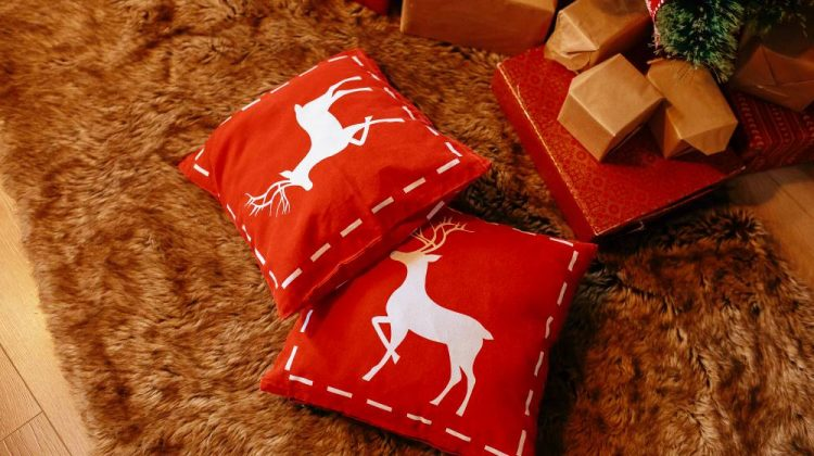 New Year's red pillows with deers lie near the Christmas tree on the floor | Decorative Christmas Pillows For Cozy And Festive Holiday Furnishing | Featured | decorative xmas pillows