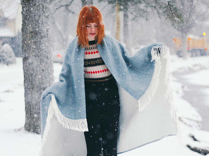 woman standing on snow covered bench while snowing | sewing for beginners