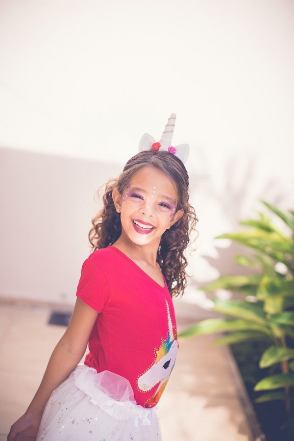girl with curly hair wearing unicorn headband, unicorn tees and skater skirt | halloween costumes for girls