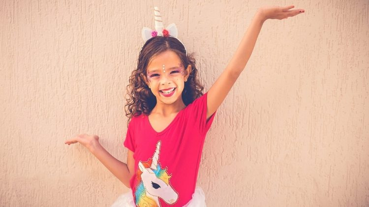 happy girl wearing unicorn headband, unicorn shirt, and tutu | 19 Easy Homemade Halloween Costumes You Can Make For Your Kids | Featured