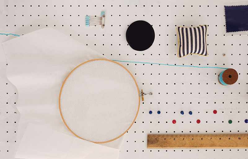 sewing equipment hanging on peg board | diy sewing room organization ideas
