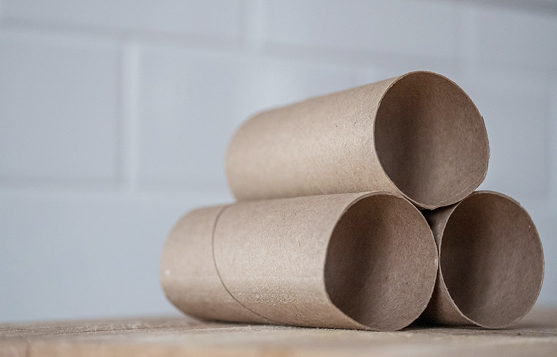 stack of carton rolls on table   diy sewing room organization ideas
