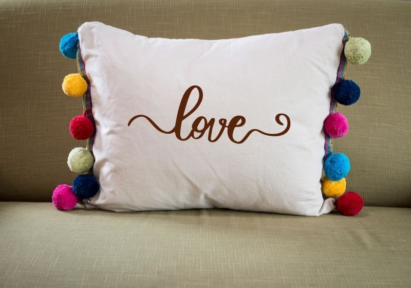 Front View of White Pillow with Colorful Pompoms on Sides | rectangle throw pillow covers