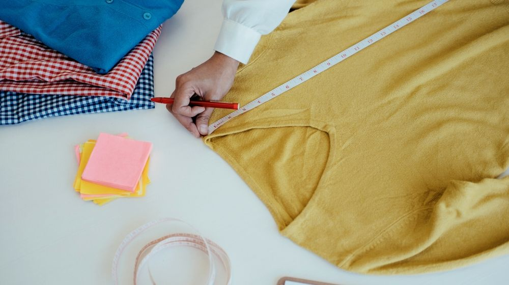 designer measuring long sleeve shirt   How To Alter Clothes That Are Big I Sewing Tips For Beginners