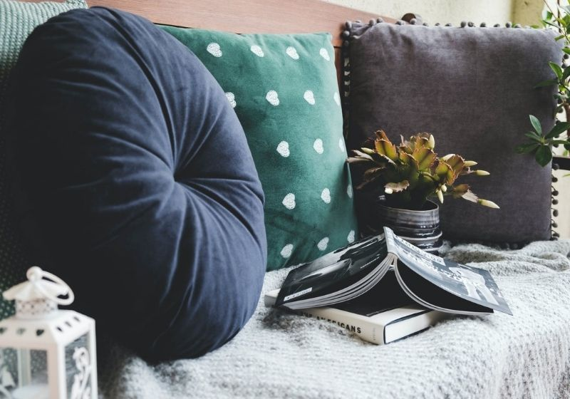 two books beside three assorted-color pillows | best throw pillow