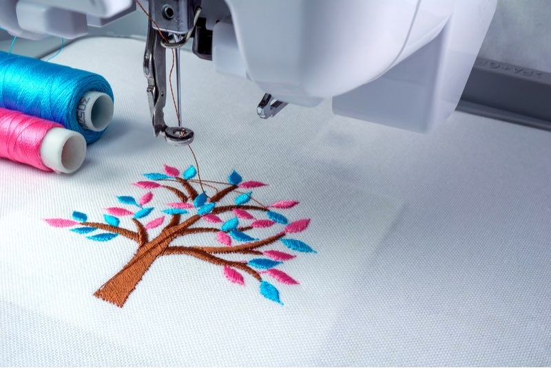 Close up picture workspace of embroidery machine show embroider tree design theme. And two thread s cyan and pink color- embroidery supplies-ss-featured