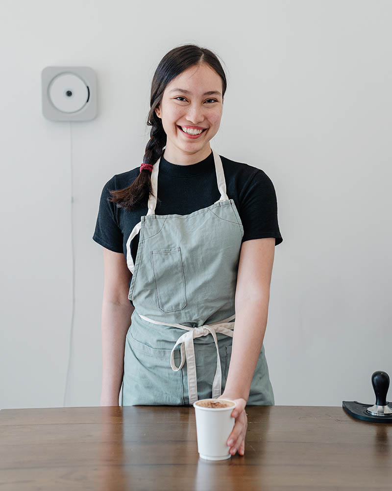 happy ethnic female barista offering coffee in paper cup | apron pattern