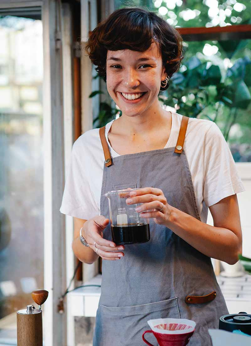 happy woman in apron with jug of coffee smiling at camera | apron pattern