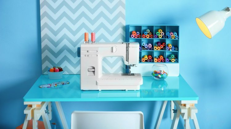 Sewing machine with fabric on table in tailor workshop | Space Saving Sewing Tables For Small Areas | Featured