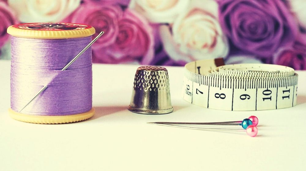 thimble purple thread measuring tap needle pins and pink and purple flowers | How to Sew By Hand In 6 Easy Steps