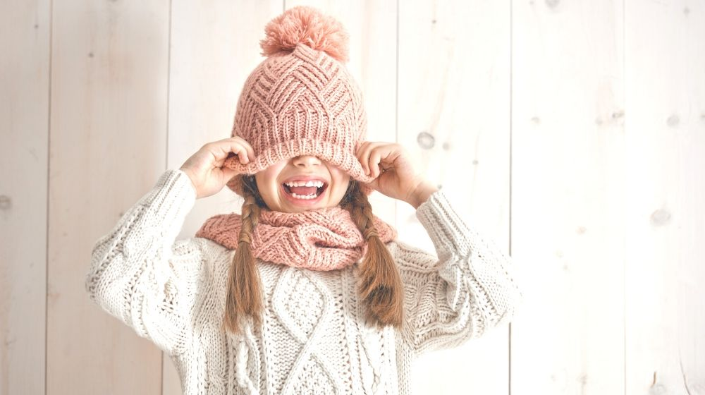 winter portrait happy little girl wearing knitted hat | Fun Sewing Ideas For Moms and Kids