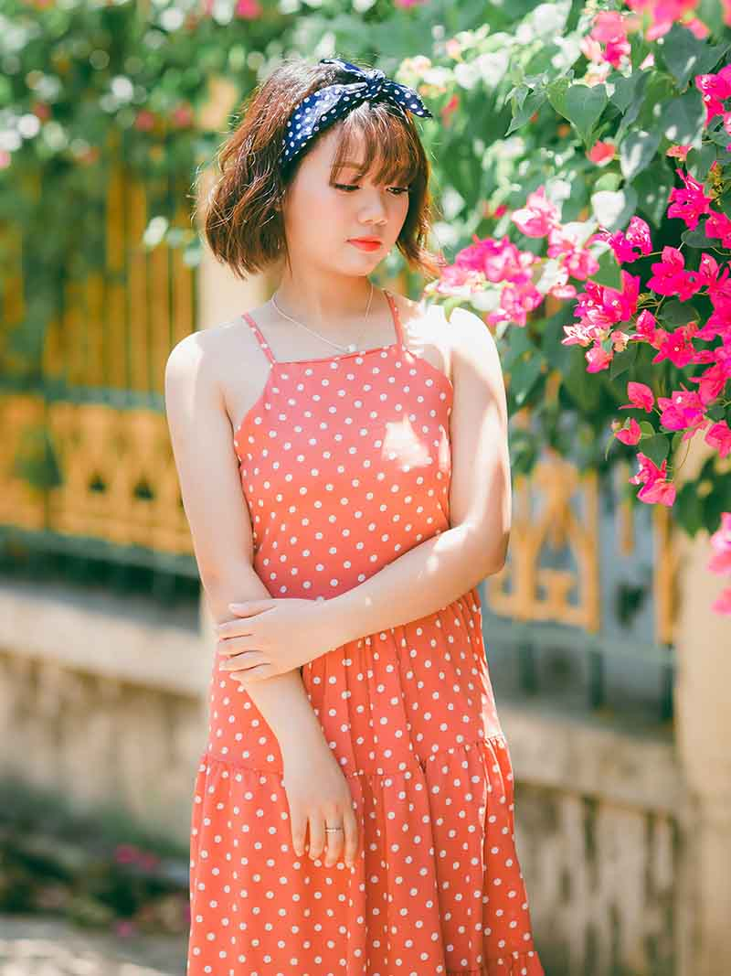 woman in orange polka dot spaghetti strap dress standing near flowers | easy sewing projects for beginners