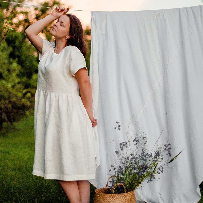 woman in white dress standing on green grass field | easy sewing projects for beginners