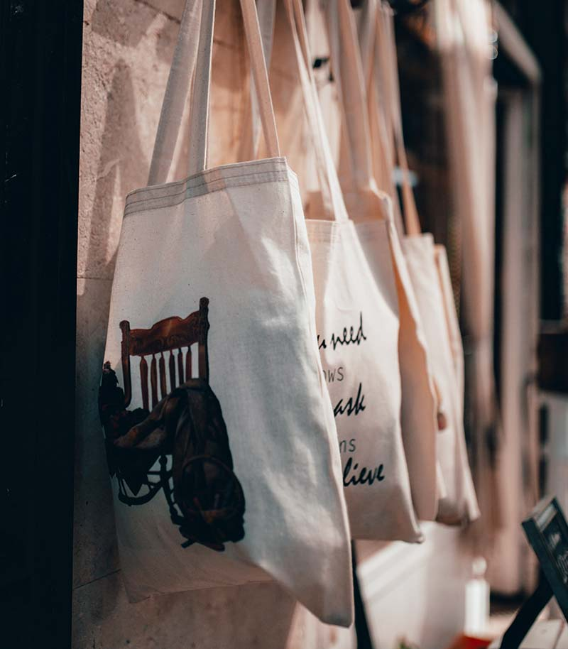 cloth tote bags with assorted prints hanging on a rack | easy sewing projects for beginners