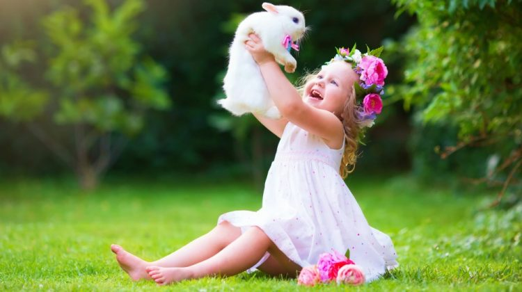 Girl playing with real rabbit in sunny garden | Easter Dresses For Girls | Free Patterns You Can Use For Sewing | kid easter dresses | Featured
