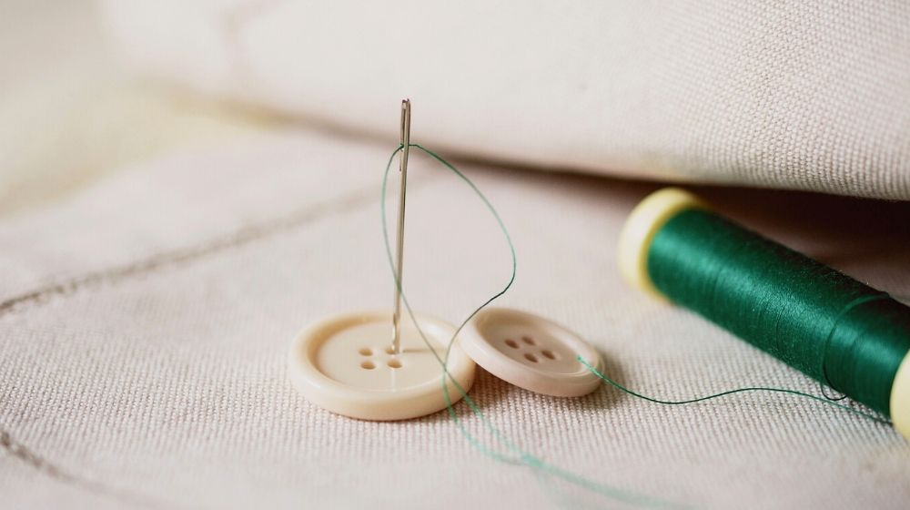 needles and button while tailoring fabric | How To Sew A Button Like An Expert