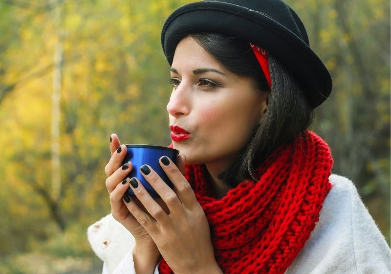 Beautiful woman in a white coat, crochet Red scarf and black hat holds a cup in her hands | free crochet scarf patterns