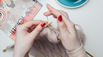 person knitting beige garment   What Is Cable Knit And How Is It Done   Featured Image