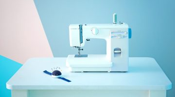 white sewing machine on the table with blue backdground | The Best Portable Sewing Machine | Top 10 Sewing Choices | Featured